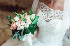 Невеста в роскошном платье свадьбы держа букет свадьбы сделанный роз Стоковое Изображение