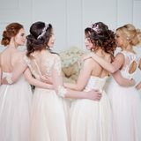 Невеста в салоне свадьбы Красивая девушка 4 в оружиях ` s одина другого Задняя часть, юбки шнурка конца-вверх Стоковые Фотографии RF
