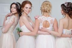 Невеста в салоне свадьбы Красивая девушка 4 в оружиях ` s одина другого Задняя часть, юбки шнурка конца-вверх Стоковые Фото