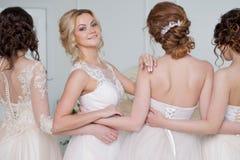 Невеста в салоне свадьбы Красивая девушка 4 в оружиях ` s одина другого Задняя часть, юбки шнурка конца-вверх Стоковое фото RF