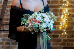 Невеста в черном халате стоя на предпосылке просторной квартиры с гирляндами и владениями букет свадьбы стоковое фото rf