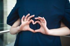 Невеста делая сердце с пальцами на grooms назад Стоковое Фото