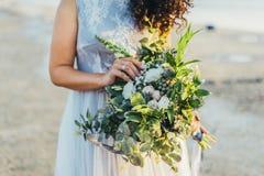 Невеста держа букет свадьбы в ее руках стоковая фотография rf