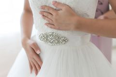 Невеста держит ее белое платье свадьбы шнурка с орнаментированным поясом стоковая фотография rf