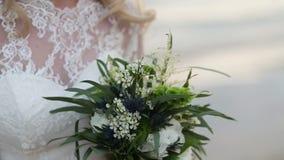 Невеста держит красивый букет На заднем плане море сток-видео