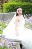 Невеста девушки в платье свадьбы с элегантным стилем причёсок, при белое платье свадьбы сидя на стенде рядом с загородкой Стоковые Фотографии RF