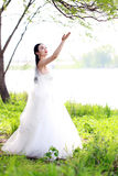 Невеста девушки в платье свадьбы с элегантным стилем причёсок, с белым платьем свадьбы Standingin трава рекой Стоковые Изображения