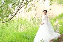 Невеста девушки в платье свадьбы с элегантным стилем причёсок, с белым платьем свадьбы Standingin трава рекой Стоковое Фото