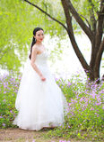 Невеста девушки в платье свадьбы с элегантным стилем причёсок, с белым платьем свадьбы Standingin трава рекой Стоковые Фото