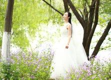 Невеста девушки в платье свадьбы с элегантным стилем причёсок, с белым платьем свадьбы Standingin трава рекой Стоковое фото RF