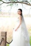 Невеста девушки в платье свадьбы с элегантным стилем причёсок, с белым платьем свадьбы Standingin трава рекой Стоковое Изображение RF