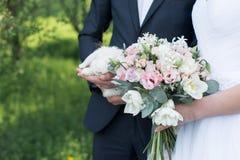 Невеста держа в ее руках чувствительный букет свадьбы с белыми и розовыми тюльпанами и розовыми малыми розами Groom держа белизну стоковые изображения