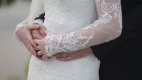 Невеста держит букет свадьбы в руках, groom обнимает ее от позади Groom обнимая невесту от позади сток-видео