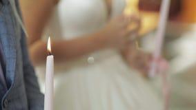 Невеста и холит стойку в церков, держа свечи в их руках видеоматериал