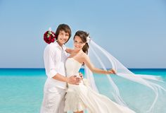 Счастливые невеста и groom на пляже стоковая фотография