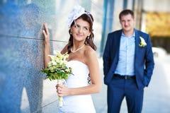 Невеста и groom стоящие близкие стена гранита Стоковые Фото