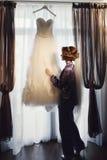 Невеста касается платью свадьбы перед класть ее дальше Стоковое фото RF