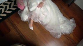 Невеста кладет дальше ее ботинки свадьбы белые на высокие пятки сток-видео