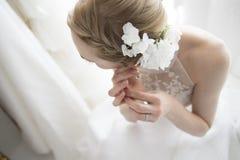 Невеста, который нужно попробовать извлечь серьги Стоковые Изображения