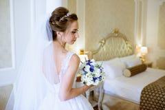 Невеста красоты в bridal мантии с букетом и шнурок вуалируют внутри помещения стоковое изображение