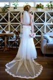 Невеста красоты в bridal мантии с букетом и шнурок вуалируют внутри помещения Стоковая Фотография RF