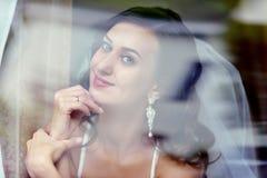 Невеста красоты в bridal мантии с шнурком вуалирует внутри помещения Стоковые Изображения