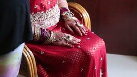 Невеста крупного плана держит руки с хной на ожиданиях коленей для церемонии