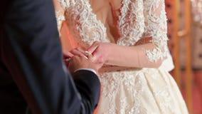 Невеста кладя обручальное кольцо на палец ` s groom видеоматериал