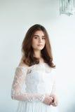 Невеста на белой предпосылке в белом платье шнурка красивейшая красотка естественная Светлый состав и свободные волосы естественн Стоковая Фотография RF