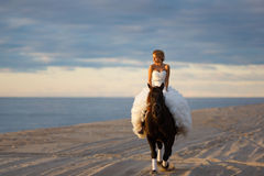 Невеста на лошади на заходе солнца морем Стоковые Изображения