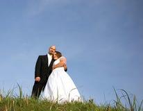 невеста обнимая травянистое удерживание холма groom Стоковая Фотография