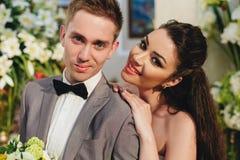 Невеста обнимая groom на предпосылке цветков Стоковые Фото