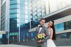 Невеста обнимая groom перед зданием Стоковые Изображения