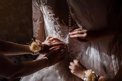 Невеста порции Bridesmaid прикрепить корсет и получать ее платье, подготавливая невесту в утре на день свадьбы стоковое изображение