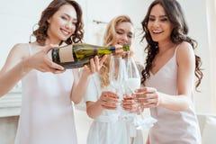 Невеста при bridesmaids лить шампанское в стеклах стоковое фото rf