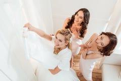 Невеста при bridesmaids смотря платье свадьбы стоковые фото