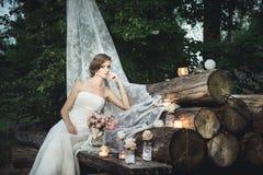 Невеста сидя элегантно на куче украшенных журналов стоковые фотографии rf
