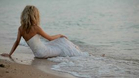 Невеста сидит на пляже видеоматериал