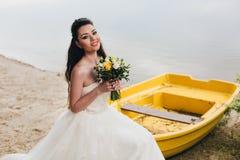 Невеста сидя на шлюпке на речном береге Стоковая Фотография RF
