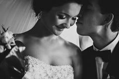 Невеста смотрит застенчивое будучи расцелованной groom Стоковая Фотография