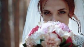 Невеста смотрит камеру, держит букет цветков около ее стороны, тогда извлекает ее, портрет, конец-вверх, замедленное движение видеоматериал