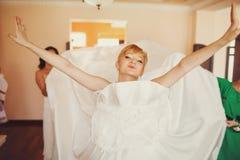 Невеста смотрит смешной надевать платье свадьбы Стоковая Фотография
