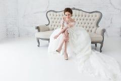 Невеста смотря вне окно, она ждет groom сидя на большой классической софе Интерьер студии просторной квартиры Minimalistic стоковые изображения