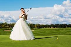 Невеста стоя на зеленом поле гольфа с древесиной стоковые изображения rf