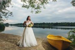 Невеста стоя около шлюпки Стоковые Фото