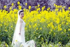 Невеста с белым платьем свадьбы в поле цветка рапса Стоковая Фотография