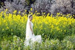 Невеста с белым платьем свадьбы в поле цветка рапса Стоковые Изображения