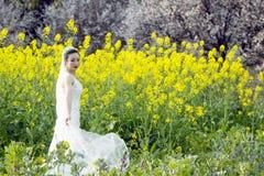 Невеста с белым платьем свадьбы в поле цветка рапса Стоковое Изображение RF
