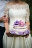Невеста с вкусным фиолетовым свадебным пирогом Стоковые Изображения