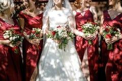 Невеста с bridesmaids на парке на день свадьбы стоковые фотографии rf